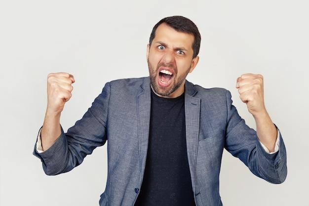Giovane uomo d'affari con la barba arrabbiata e folle, alzando i pugni, frustrato e furioso, urlando di rabbia.