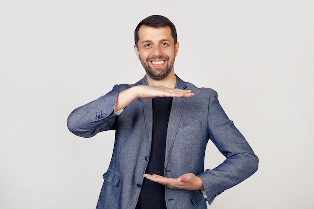 Giovane uomo d'affari con la barba in una giacca, gesticolando con le mani mostrando un segno di grandi e grandi dimensioni un simbolo di misura.