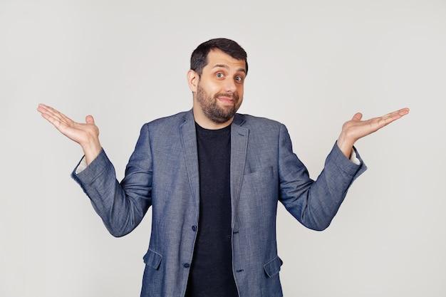 Un giovane uomo d'affari con la barba in una giacca, alza le spalle, le braccia tese completa incredulità, dubita di poter dire la risposta non ne ho idea non lo so