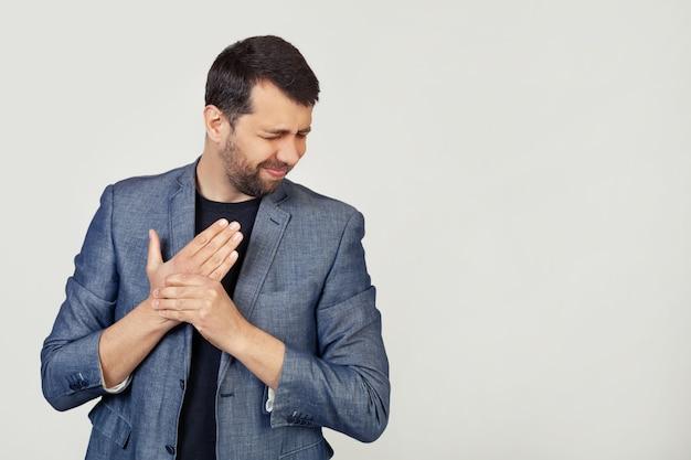 Uomo giovane uomo d'affari con la barba in una giacca, soffre di dolori alle mani e alle dita, infiammazione dell'artrite.