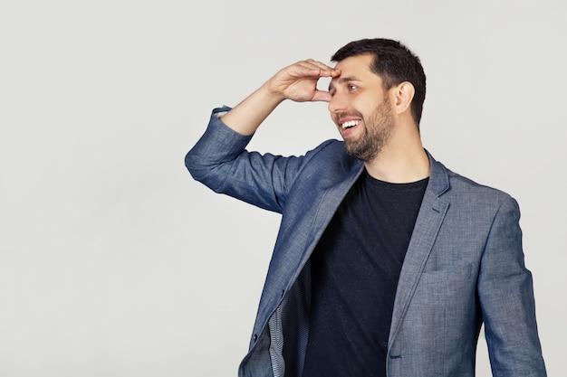 Giovane uomo d'affari con la barba in una giacca, molto felice e sorridente, guardando lontano con la mano sopra la sua testa.