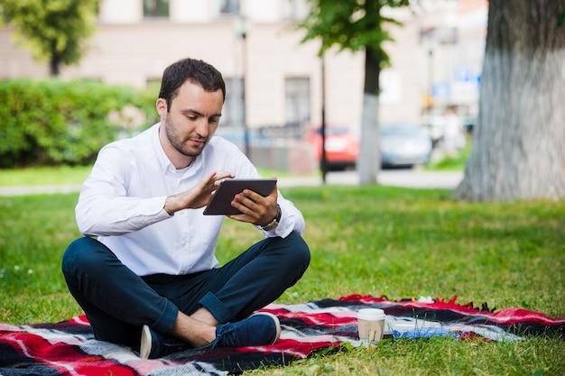 Giovane uomo d'affari presso il parco lavorando con tablet