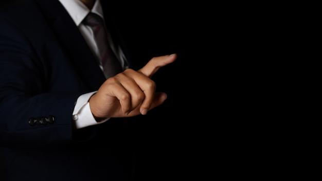Giovane uomo d'affari che punta il dito toccando sullo sfondo dello schermo nero. copia spazio.