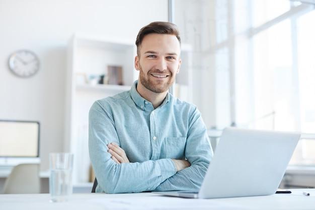 Giovane imprenditore in posa sul posto di lavoro