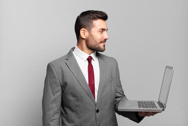 Giovane uomo d'affari sulla vista di profilo che cerca di copiare lo spazio davanti, pensare, immaginare o sognare ad occhi aperti e in possesso di un computer portatile