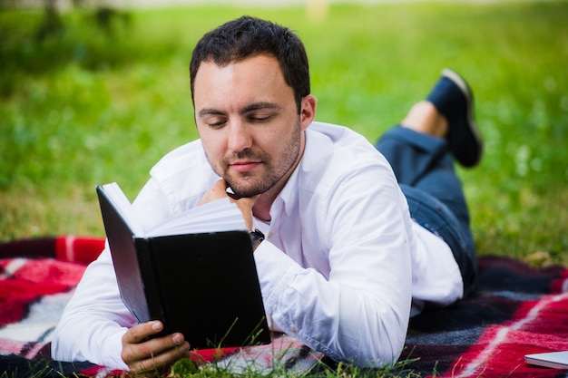 Libro di lettura del giovane uomo d'affari che si trova nel parco