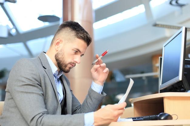Giovane uomo d'affari che legge documenti alla scrivania in ufficio.