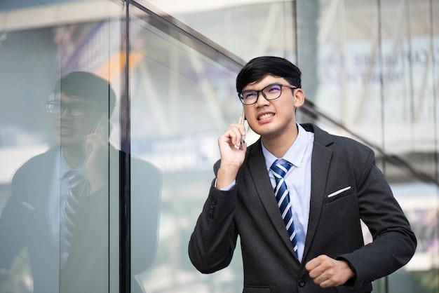 Giovane uomo d'affari che funziona mentre parla al telefono cellulare durante l'ora di punta.