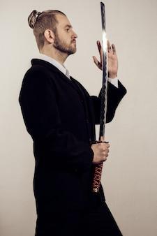 Samurai del giovane uomo d'affari in un vestito nero con una spada giapponese