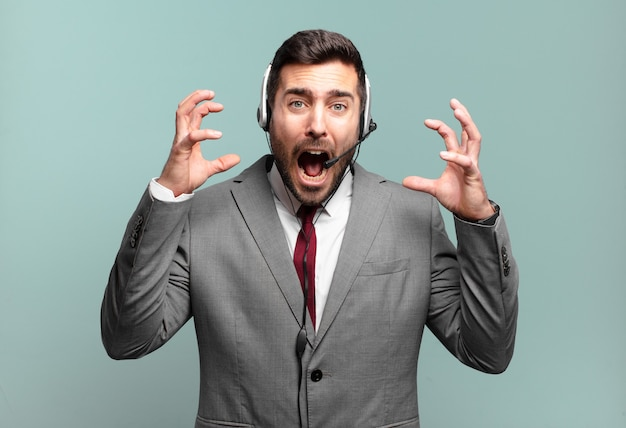 Giovane uomo d'affari che grida con le mani in alto, sentendosi furioso, frustrato, stressato e sconvolto il concetto di telemarketing