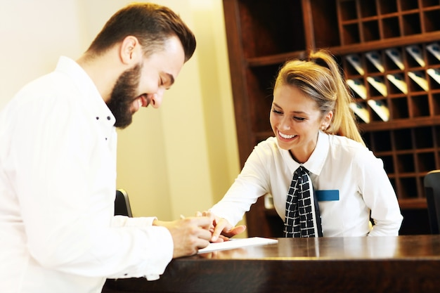 Giovane uomo d'affari che firma il conto in hotel?