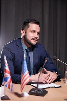 Il giovane uomo d'affari si siede parlando nel microfono alla riunione, offrendo nuove idee e soluzioni per lo sviluppo del business. nell'ufficio moderno della sala riunioni