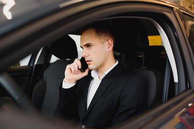 Il giovane uomo d'affari si siede in auto di lusso e parla al telefono.