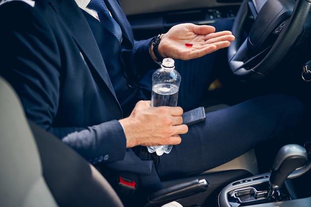 Giovane uomo d'affari seduto nella sua macchina e prendendo medicine mentre ha mal di testa
