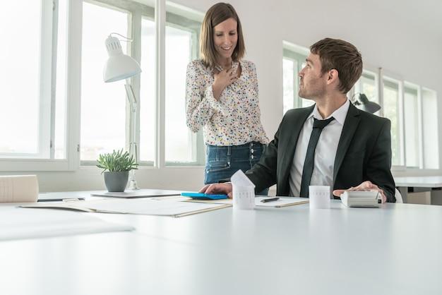 Giovane uomo d'affari seduto alla scrivania dell'ufficio che esamina il rapporto finanziario e la sua compagna in piedi accanto a lui in una discussione.