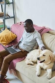 Giovane uomo d'affari seduto sul divano con il cane e lavora online al computer a casa