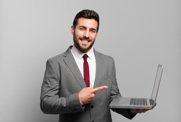 Giovane imprenditore sorridendo allegramente, sentendosi felice e indicando di lato e verso l'alto, mostrando l'oggetto nello spazio della copia e tenendo in mano un laptop