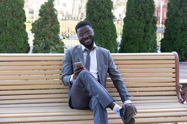 Il giovane imprenditore sorridente sulla panchina della città con telefono, tablet