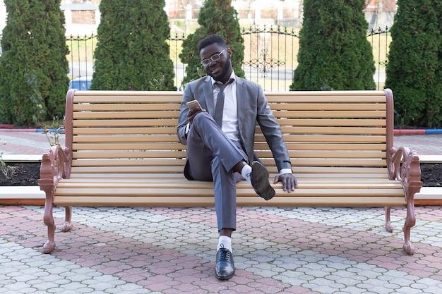 Il giovane imprenditore sorridente sulla panchina della città con il telefono