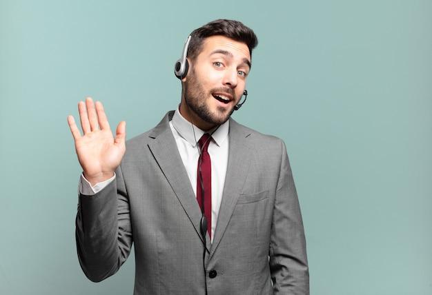Giovane uomo d'affari che sorride allegramente e allegramente, agitando la mano, dandoti il benvenuto e salutandoti o dicendo addio al concetto di telemarketing