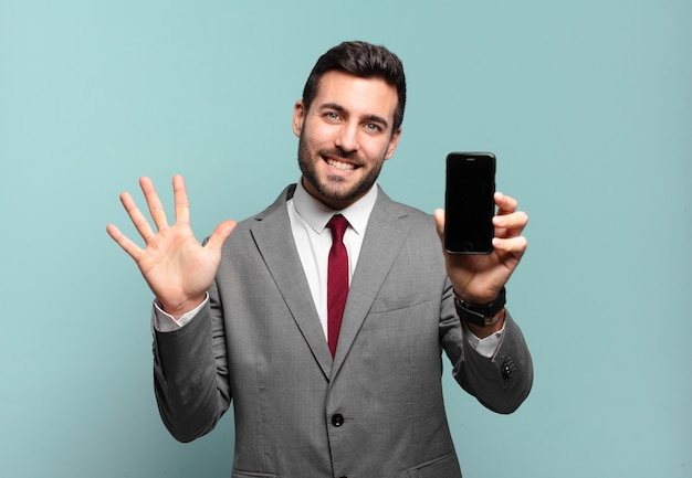 Giovane imprenditore sorridente e guardando amichevole, mostrando il numero cinque o quinto con la mano in avanti, il conto alla rovescia e mostrando il suo schermo del telefono