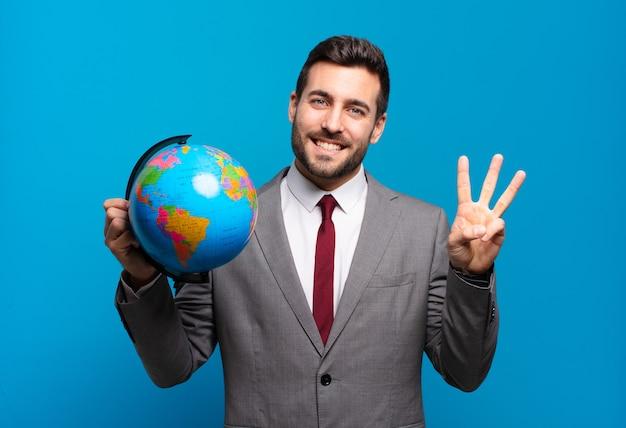 Giovane uomo d'affari che sorride e che sembra amichevole, mostrando il numero tre o terzo con la mano in avanti, contando alla rovescia tenendo una mappa del globo del mondo