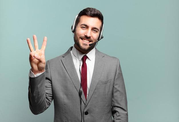 Giovane uomo d'affari sorridente e dall'aspetto amichevole, mostrando il numero tre o il terzo con la mano in avanti, contando il concetto di telemarketing