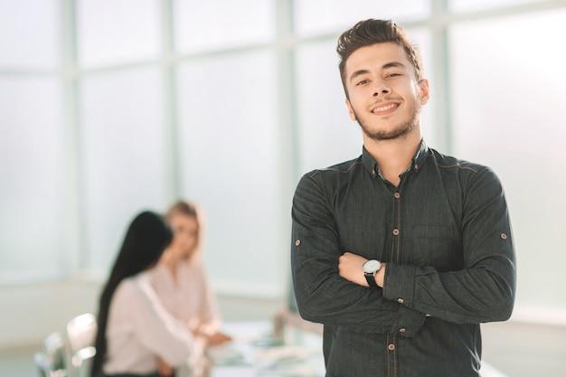 Giovane imprenditore in piedi nel suo ufficio. foto con copia spazio
