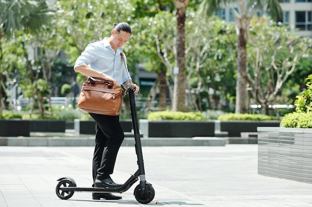 Giovane imprenditore in piedi sullo scooter e il controllo del documento nella sua borsa in pelle