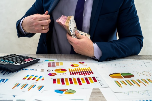Il giovane uomo d'affari in tuta conta i soldi della grivna e lavora con grafici e documenti come reddito mensile netto. il concetto di denaro è stipendio o corruzione. lavoro in ufficio.