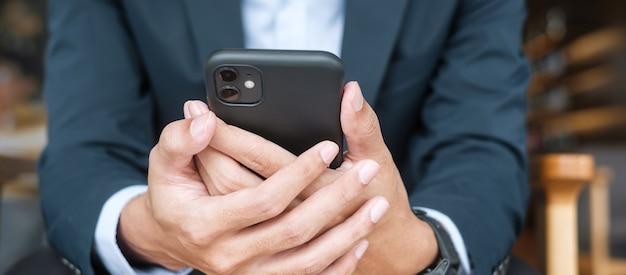Giovane uomo d'affari in tuta che tiene in mano e utilizza lo smartphone per i messaggi sms, l'uomo che digita il telefono cellulare touchscreen in ufficio o al bar. business, stile di vita, tecnologia e concetto di rete di social media