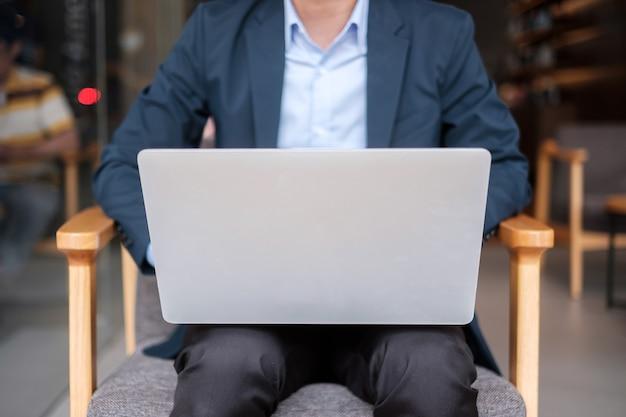 Giovane uomo d'affari in tuta con laptop, uomo che digita tastiera computer notebook in ufficio o caffè business, tecnologia e concetto di freelance