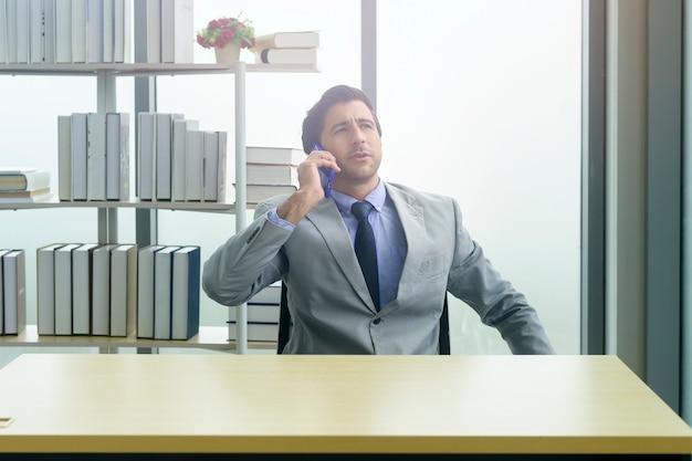 Giovane uomo d'affari in tuta che utilizza smartphone in un ufficio moderno