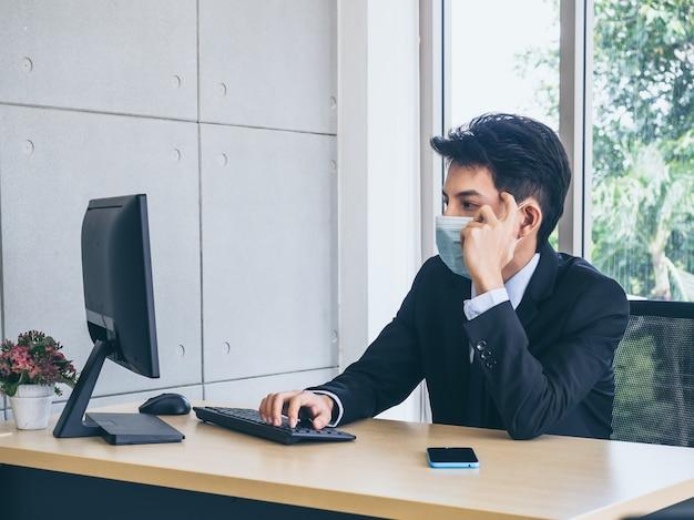 Giovane uomo d'affari in vestito che indossa la maschera protettiva che lavora al computer e pensa con sforzo con il viso stanco con lo smartphone sulla scrivania in ufficio vicino all'enorme finestra di vetro.