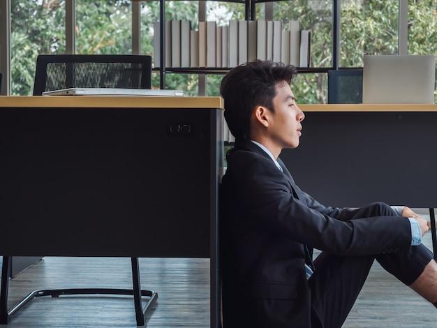 Giovane uomo d'affari in vestito con problemi, noioso seduto stanco, stressato e triste con distratto a terra in ufficio.