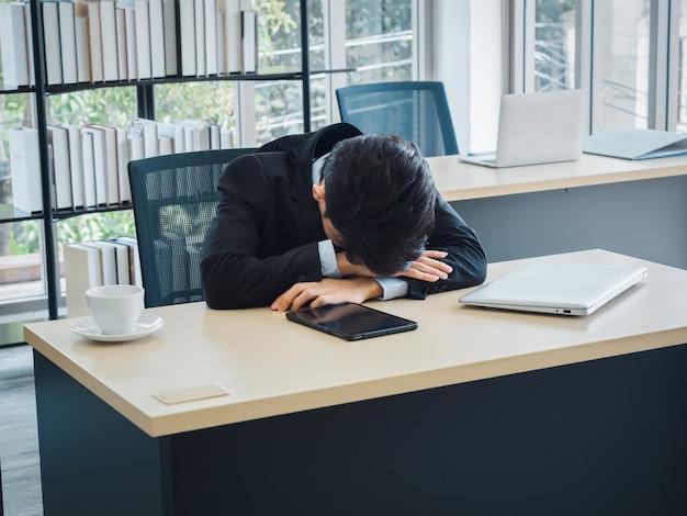 Giovane uomo d'affari in vestito con problemi, noioso stanco, stressato e triste seduto con la testa in giù sulla sua scrivania in ufficio.