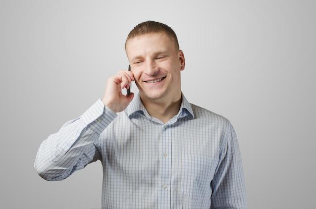 Giovane imprenditore a parlare su un telefono cellulare. isolato sulla superficie bianca