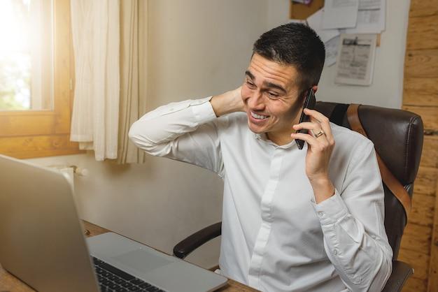 Il giovane imprenditore parla al telefono e si sente in colpa, preoccupato per un problema sul lavoro, ha messo la mano dietro la testa.