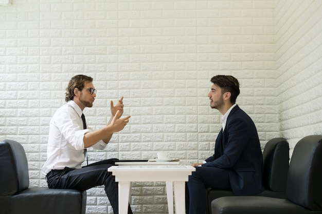 Giovane uomo d'affari parlando di lavoro con il collega in un salotto moderno di affari. persone che lavorano in affari.