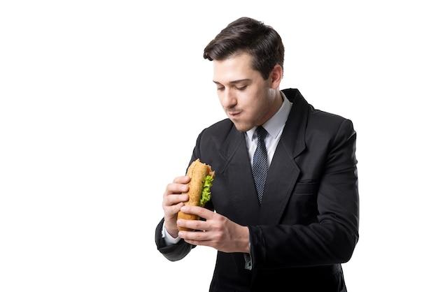 Giovane imprenditore in cravatta e abito nero mangia hot dog, isolato su bianco