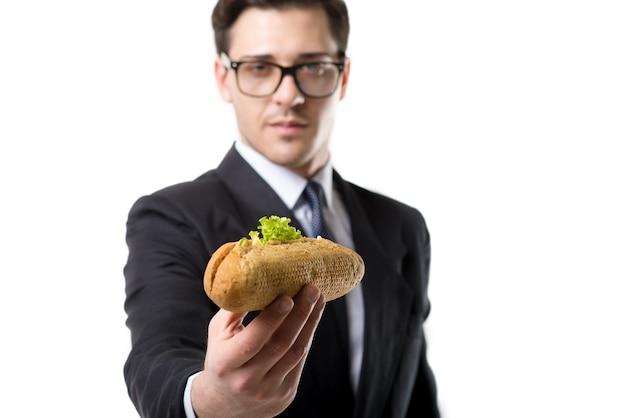 Giovane uomo d'affari in cravatta e vestito mangia hot dog