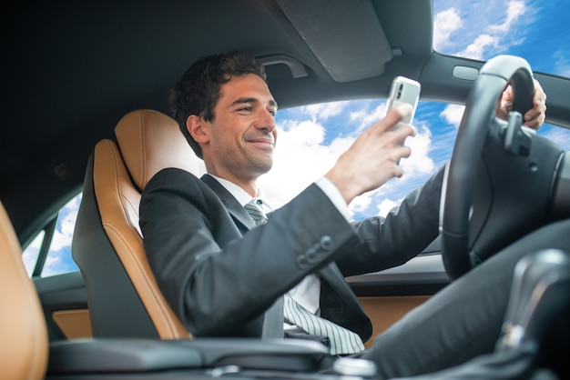 Giovane uomo d'affari che usa il suo telefono cellulare durante la guida, concetto di comportamento pericoloso