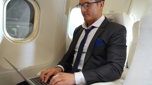 Giovane imprenditore utilizzando il computer portatile in aereo