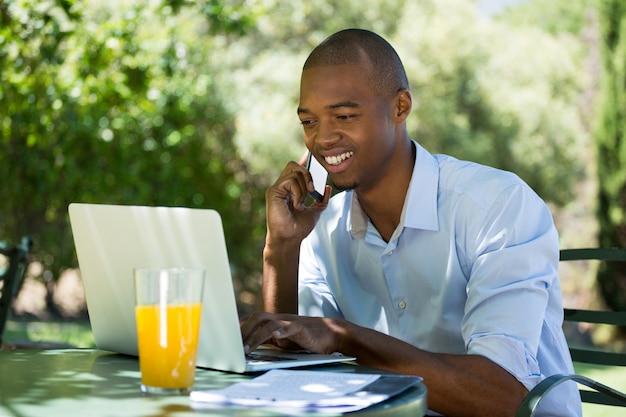 Giovane imprenditore utilizzando laptop e smart phone al ristorante all'aperto