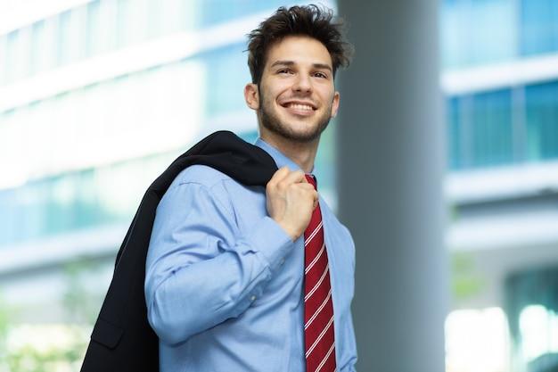 Giovane uomo d'affari che cammina e che tiene la sua giacca all'aperto