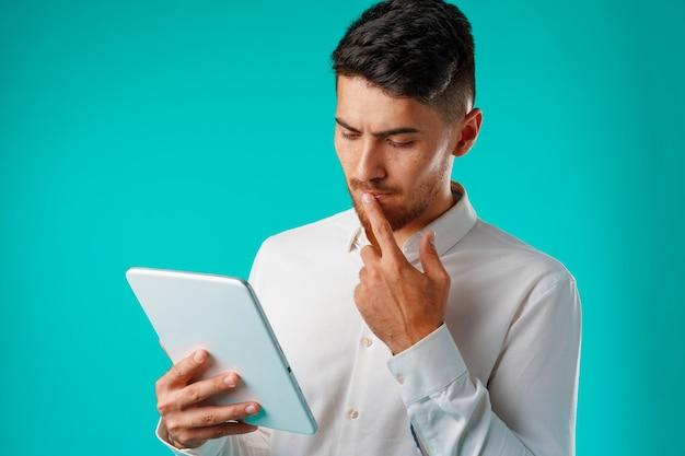 La camicia bianca da portare del giovane uomo d'affari tiene la compressa digitale contro il verde