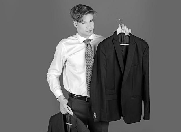 Giovane uomo d'affari in camicia bianca e cravatta, assistente di negozio presente vestito formale giacca su appendiabiti, scelta e successo, moda business.