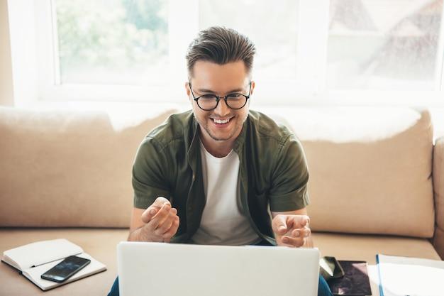 Giovane uomo d'affari con gli occhiali che hanno una riunione in linea sul computer portatile mentre si lavora con un libro e alcuni documenti