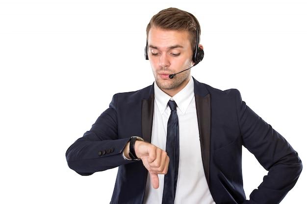Giovane uomo d'affari con una cuffia che guarda i suoi orologi