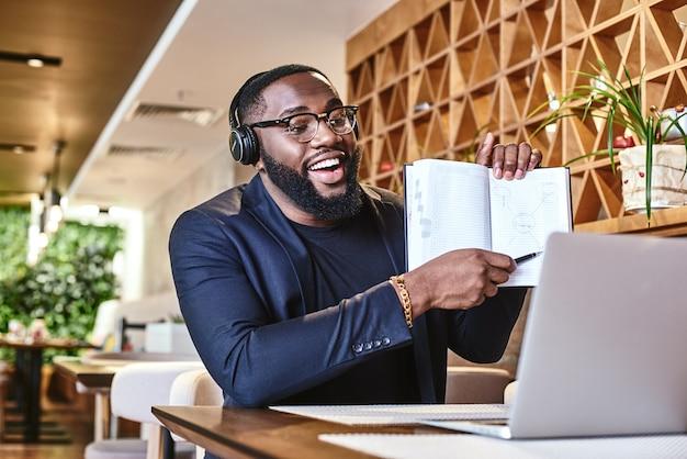 Giovane uomo d'affari con le cuffie seduto al bar davanti al laptop e alla rete